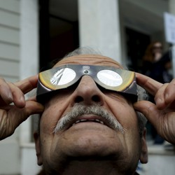 A man looks through eclipse glasses.