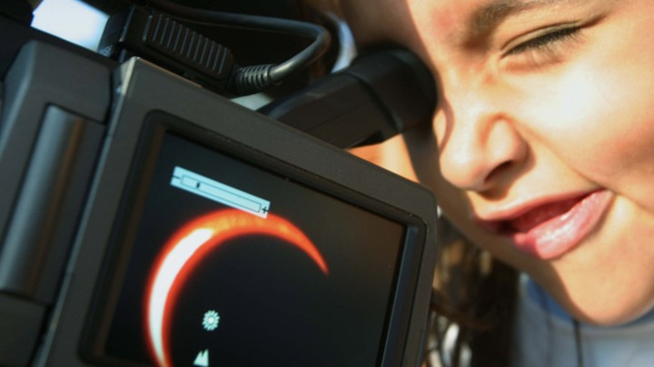 A boy watches an annular eclipse through a camera.