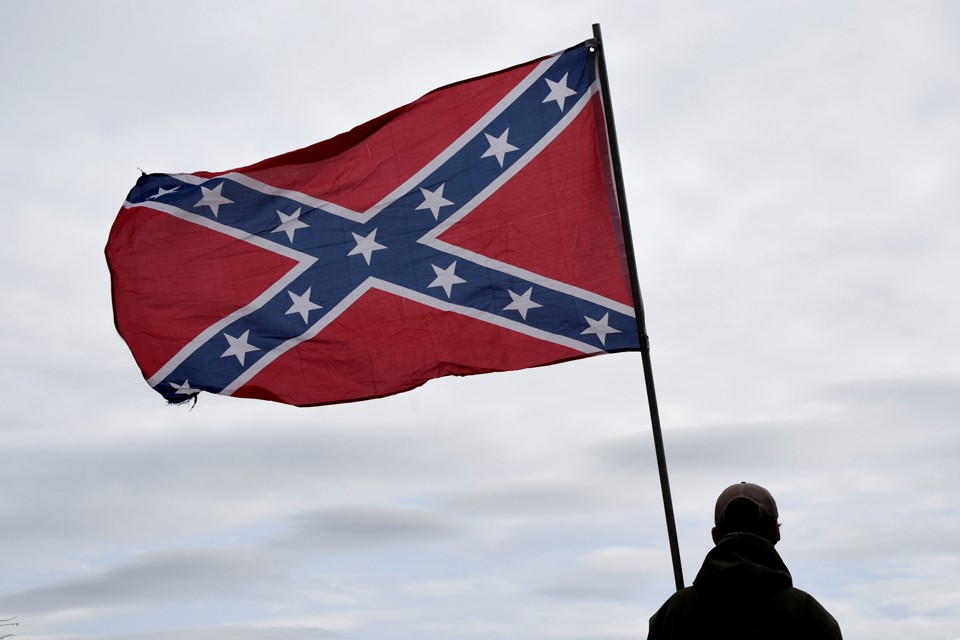 A Confederate flag waves in the wind.