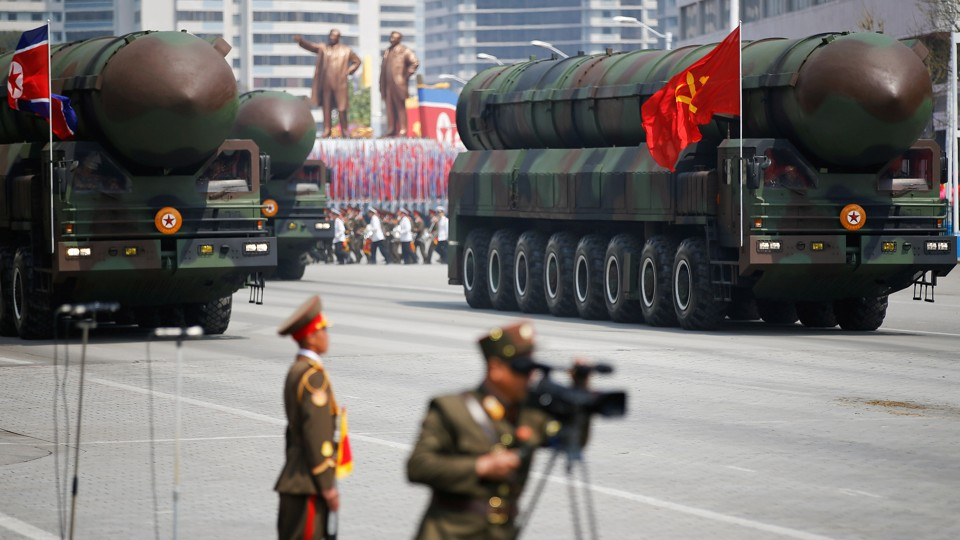 Intercontinental ballistic missiles are driven on military trucks with a North Korean military parade behind them