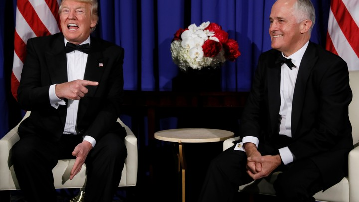 President Donald Trump and Australian Prime Minister Malcolm Turnbull sit on chairs and laugh.