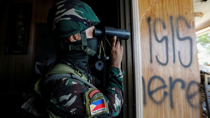 A Filipino soldier uses binoculars next to a wood panel where the words ' ISIS here' are spray-painted.