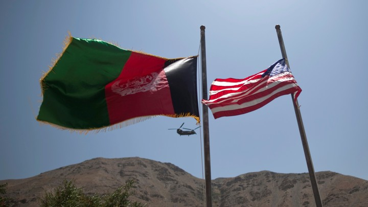 An Afghan flag flutters next to a U.S. flag  with a U.S. military helicopter in the background.