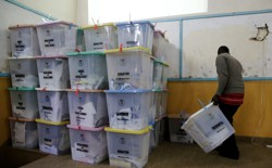 An election official from the Independent Electoral and Boundaries Commission arranges ballot boxes inside the Jamuhuri High School tallying center in Nairobi, Kenya, on August 9.