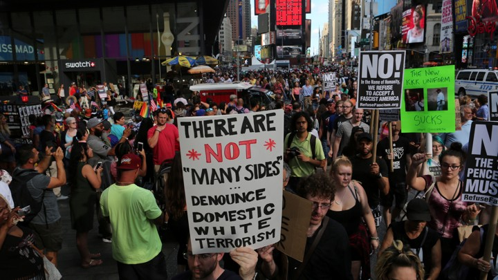 A protester holds up a sign denouncing white terrorism.