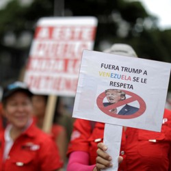 Venezuelan protesters carry a sign against President Trump