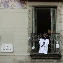 A T-shirt with a black ribbon hangs from a balcony