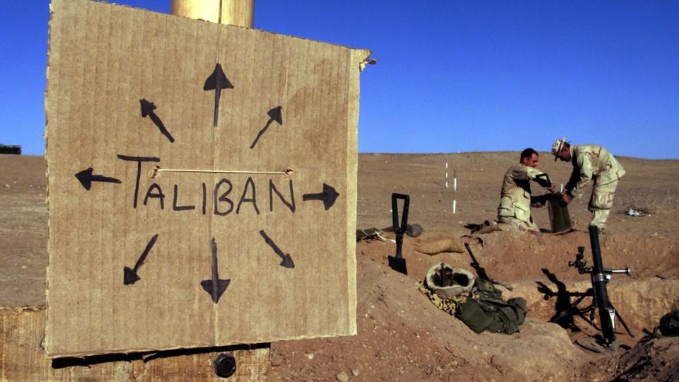 "Two Marines fill a sandbag near a sign that says ""Taliban"""
