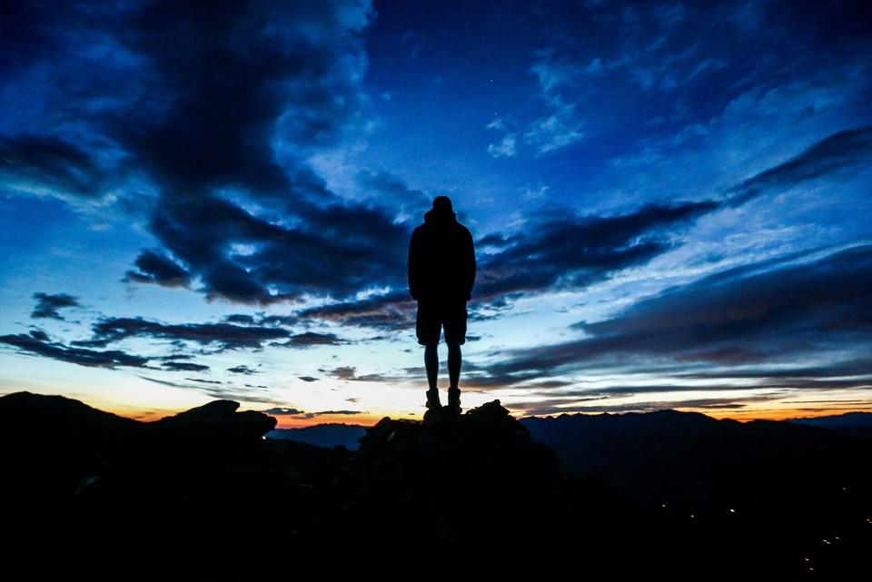 A man stands atop a cliff.