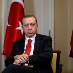 President Erdogan sits between two Turkish flags.