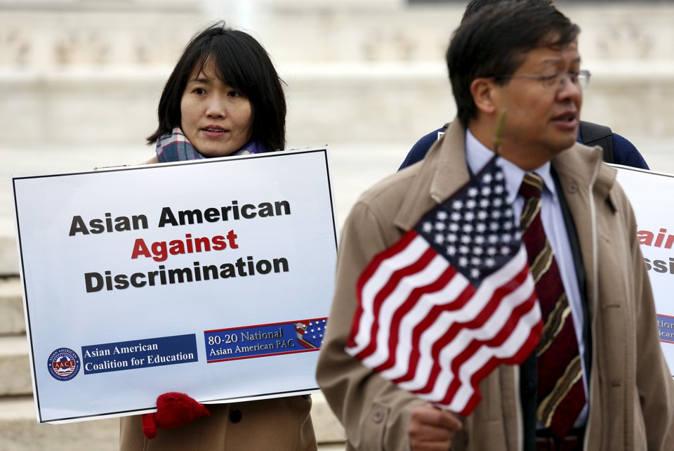 Two Asians hold signs opposing racial discrimination in college admissions outside the Supreme Court