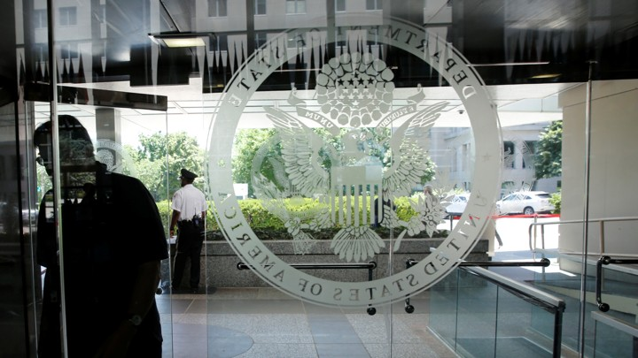 The State Department's logo on a glass door
