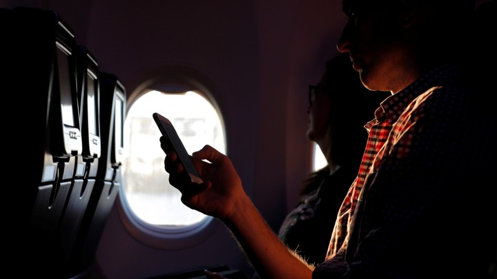 A person holds a phone while being backlit through an airplane window