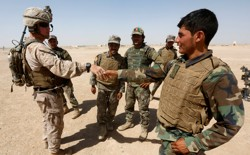 A U.S. Marine shakes hand with Afghan National Army soldiers.