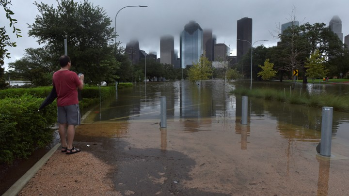 A man stands in a flooded city park, with Houston's skyline in the background