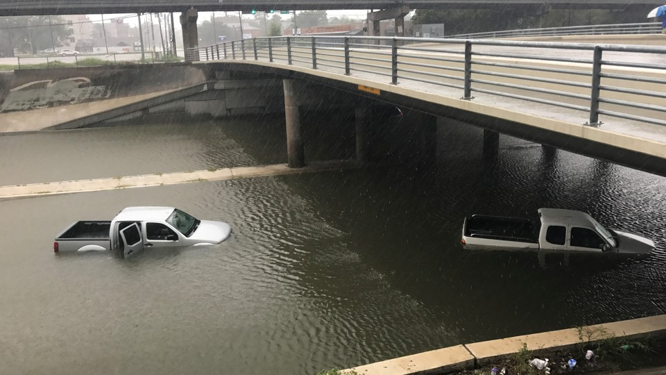 Trucks partially submerged on a flooded highway in Texas.