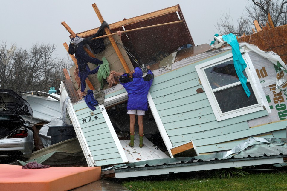 A woman stands on a destroyed house in Fulton, Texas.
