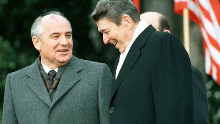 President Ronald Reagan stands with former Soviet leader Mikhail Gorbachev and laugh in front of an American flag.