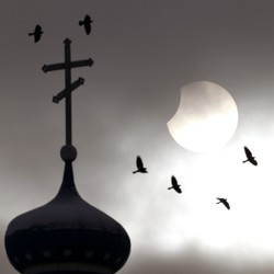 Birds fly past a church spire in front of a partially eclipsed sun.