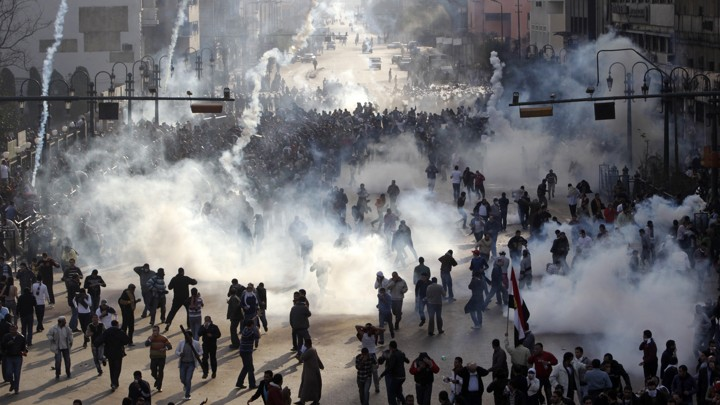 Protesters flee from tear gas fire during clashes in Cairo.