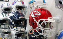 A bunch of football helmets hang on a wall.