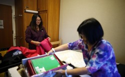 A student and her mom are unpacking in a dorm room.