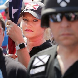 Standing behind a man in a helmet, a woman holds a flag at a rally in Charlottesville, Virginia
