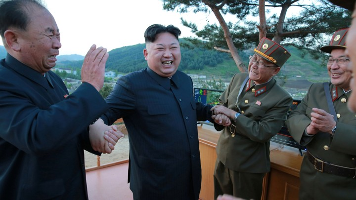 North Korean leader Kim Jong Un reacts with scientists and engineers.