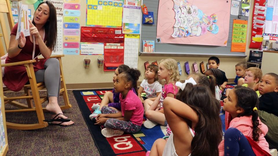 A kindergarten teacher reads to students.
