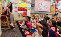 A kindergarten teacher reads to students.