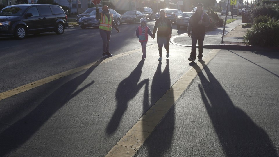 Parents cross the street with their children.