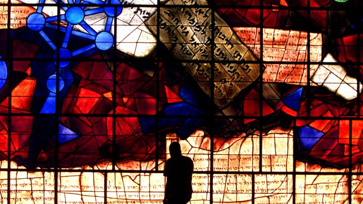 A student is silhouetted against the Ardon Windows, which contain imagery derived from the Zohar, in the library of the Hebrew University of Jerusalem.
