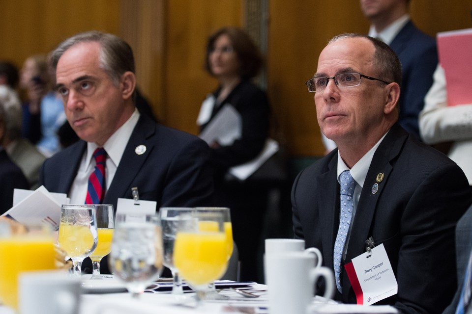 Veterans Affairs Secretary David Shulkin and award winner Rory Cooper sit at a table at the 2017 Sammies finalist-announcement breakfast.