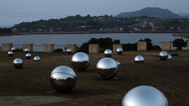 A memorial made of large metallic silver balls overlooking a bay and seaside town