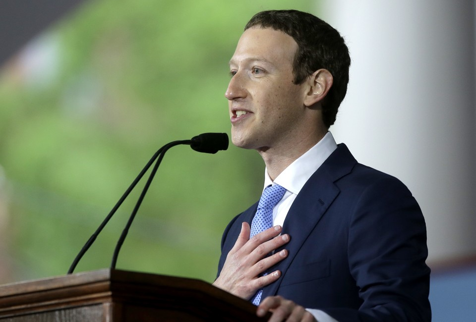 Mark Zuckerberg speaks at a podium with a hand over his heart.