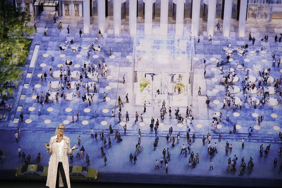An Apple speaker stands in front of a screen depicting people gathered in a town square