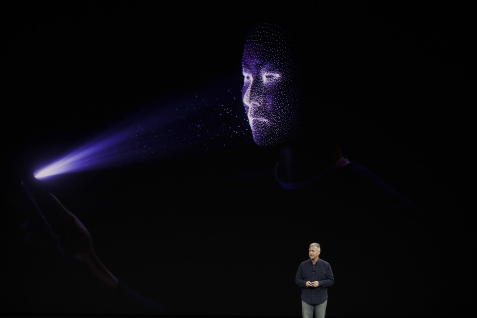 Phil Schiller stands in front of a screen demonstrating the Face ID feature of the iPhone X.