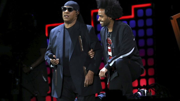 Stevie Wonder, left, kneels on stage next to his son Kwame Morris before performing at the Global Citizen Festival in Central Park on Saturday, Sept. 23, 2017, in New York.