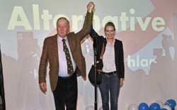 AfD top candidates Alexander Gauland and Alice Weidel hold hands in triumph in front of an AfD sign and balloons.
