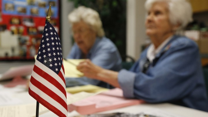 An American flag sits on the table where two Oklahoma poll workers are helping voters.