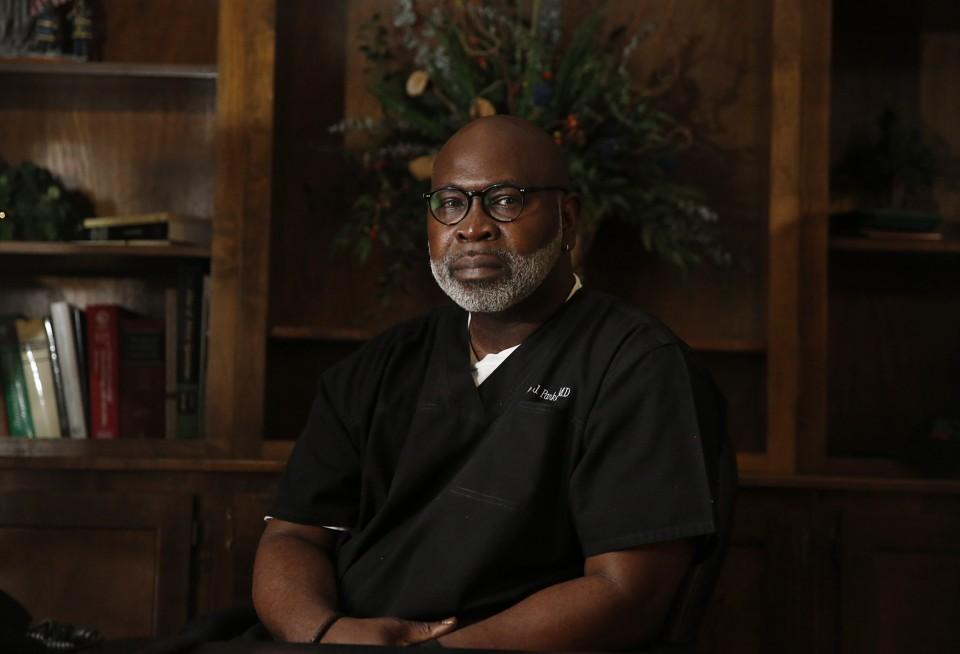 Willie Parker wears scrubs in an office.