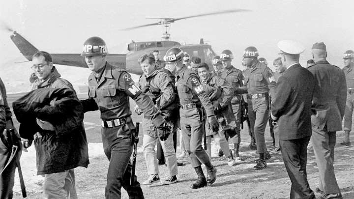 Released crewmen of the USS Pueblo are escorted by MPs off a helicopter.