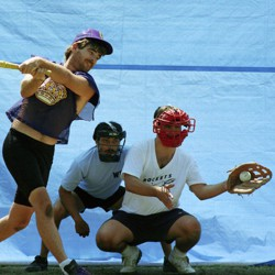 A player at bat strikes out while a Wiffle ball rests in the catcher's mitt.