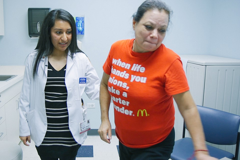A woman in a lab coat supports a woman in a T shirt in a doctor's office.