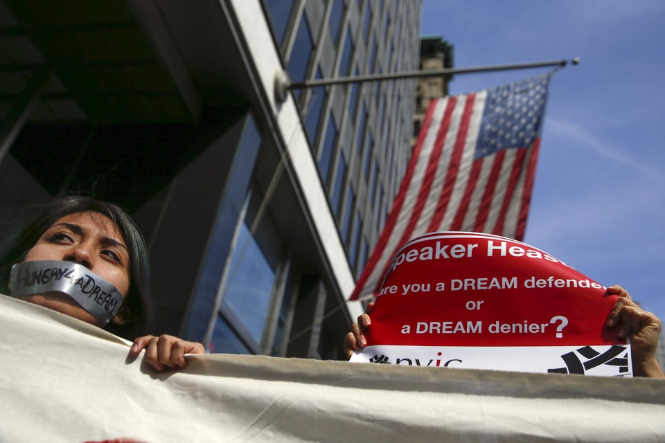 "A young woman with tape on her mouth that reads ""Hungry4aDream"" stands in front of an American flag."