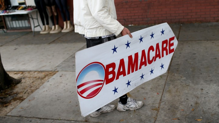 A person holds an Obamacare sign