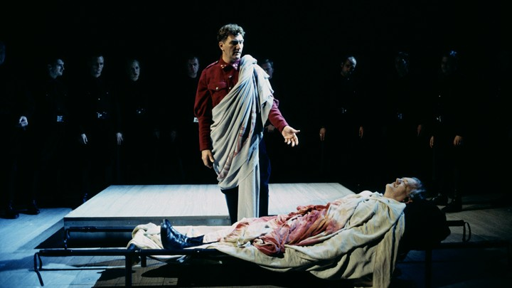 A bloody actor lies on a cot while another actor speaks and others look on.
