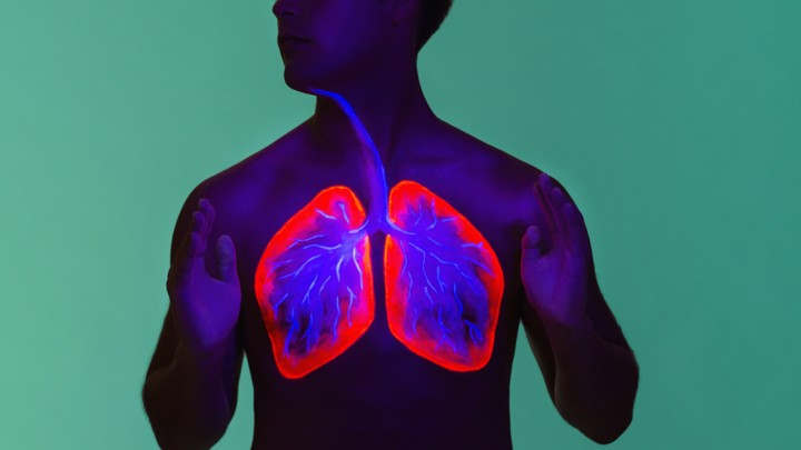 A shirtless man with his lungs highlighted in neon colors