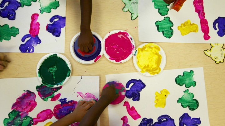 Children use stamps dipped in paint to make art.