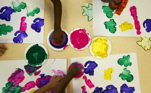 Children Use Stamps Dipped In Paint To Make Art